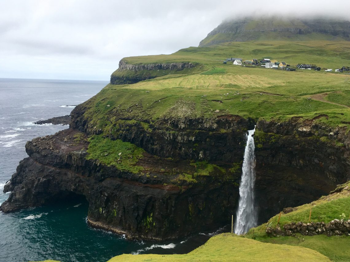 The beautiful waterfall of Múlafossur, in the village of Gásadalur, sits tucked away between lush green fields and soaring mountains to all sides and plunges directly into the Atlantic Ocean. (c) Kate Chapman